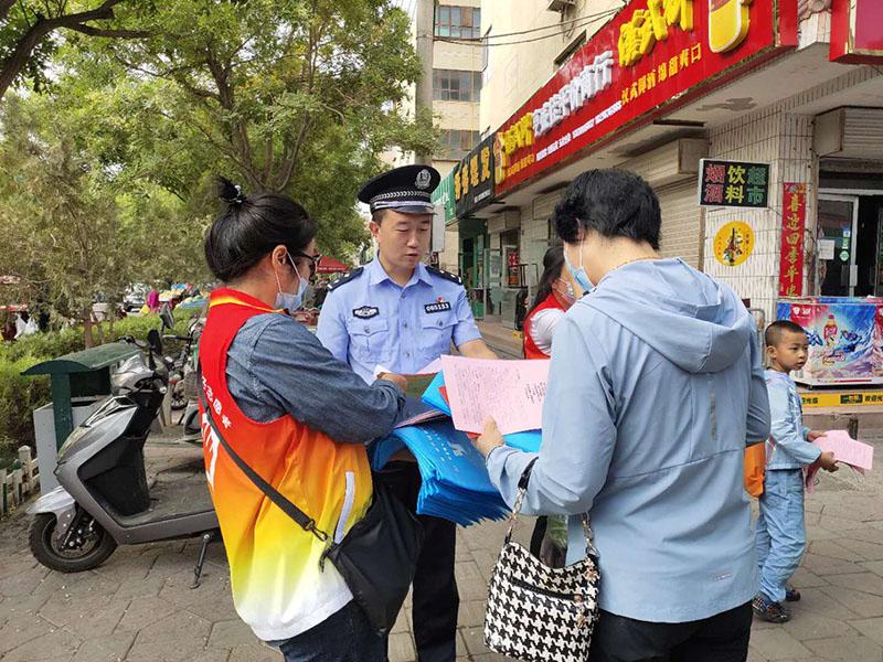 图为:社区民警和志愿者在人员较多的市场宣传防电诈知识.jpg